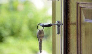 klucz wsadzony w zamek w drewnianych drzwiach